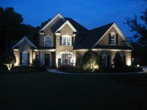 Front of home lit with landscape lighting.